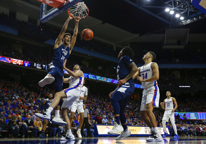 Nevada forward Trey Porter (15) dunks the ball over Boise State forward David Wacker (33) during the first half of an NCAA college basketball game, Tuesday, Jan. 15, 2019, in Boise, Idaho. (AP Photo/Steve Conner)