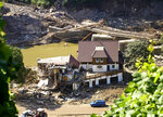 A house is completely torn open after the flood, behind it a destroyed bridge can be seen in Marienthal, Germany, Wednesday, July 21, 2021. The flood has also destroyed numerous houses here. (Thomas Frey/dpa via AP)