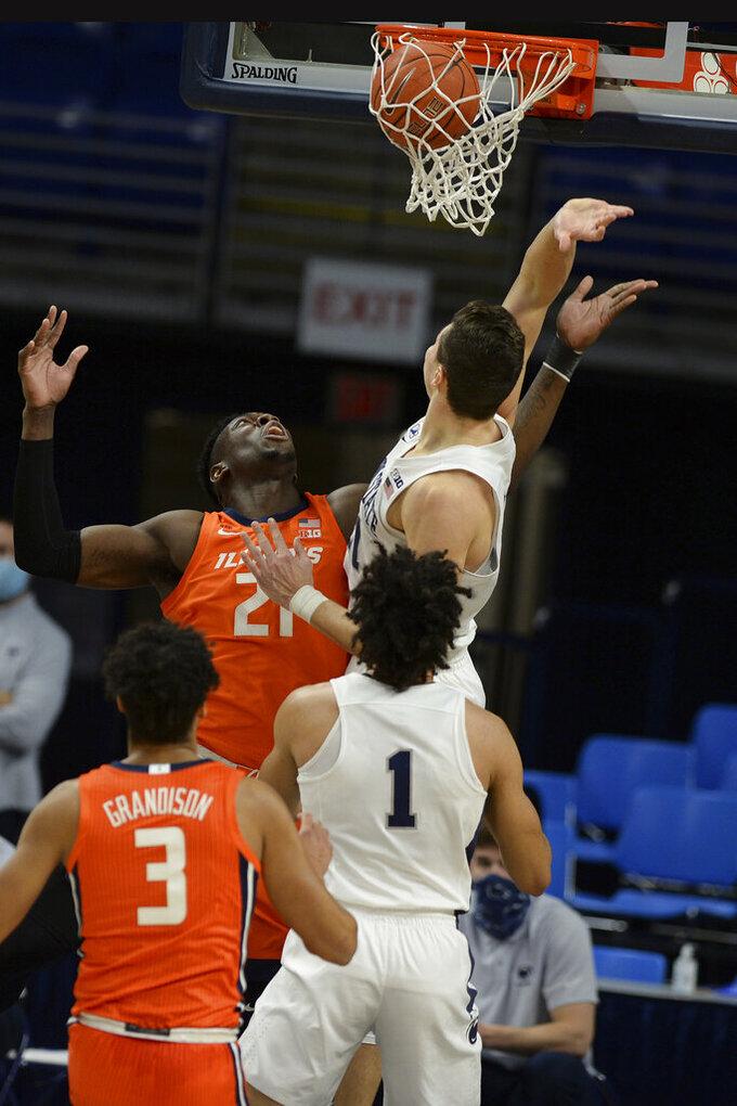 Illinois' Kofi Cockburn (21) scores on Penn State's John Harrar (21) during the first half of an NCAA college basketball game Wednesday, Dec. 23, 2020, in State College, Pa. (AP Photo/Gary M. Baranec)