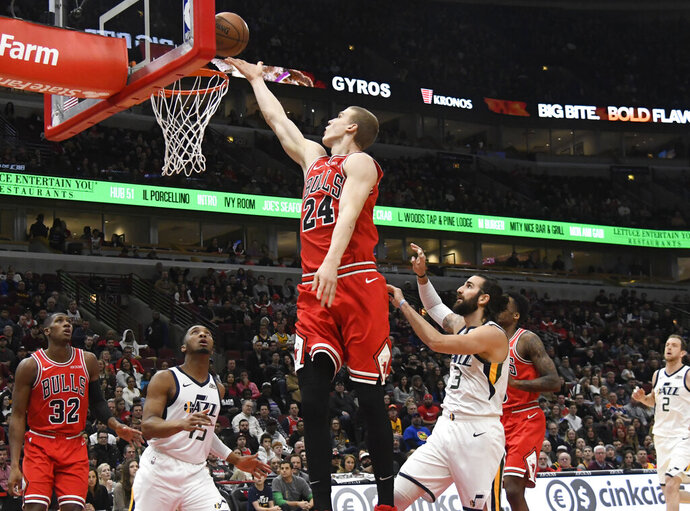 Chicago Bulls forward Lauri Markkanen (24) goes to the basket as Utah Jazz guard's Donovan Mitchell (45) and guard Ricky Rubio (3) defend him during the first half of an NBA basketball game Saturday, March 23, 2019, in Chicago. (AP Photo/David Banks)
