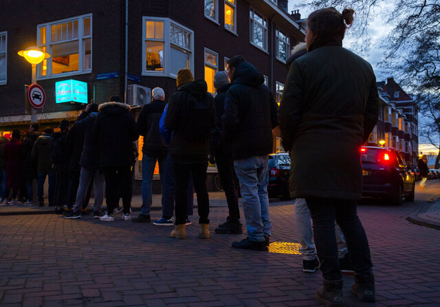 People queue to buy marijuana at  the coffeeshop Bulwackie in Amsterdam, Netherlands, Sunday, March 15, 2020, after a TV address by health minister Bruno Bruins who ordered all Dutch schools, cafes, restaurants, coffeeshops and sport clubs to be closed on Sunday as the government sought to prevent the further spread of coronavirus in the Netherlands. For most people, the new coronavirus causes only mild or moderate symptoms, such as fever and cough. For some, especially older adults and people with existing health problems, it can cause more severe illness, including pneumonia. (AP Photo/Peter Dejong)