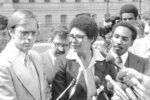 FILE - In this April 4, 1980, file photo, Anita DeFrantz, spokeswoman for the U.S. Olympic Committee's Athletes Advisory Council, flanked by Larry Hough, left, and  Fred Newhouse right, answers questions for reporters outside the White House in Washington, after White House officials rejected a proposal that would have allowed American athletes to compete at the summer Olympic Games in Moscow. (AP Photo/File)