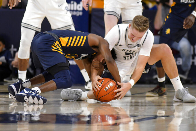 North Carolina A&T guard Kameron Langley, left, and Utah State guard Sam Merrill scramble for a the ball during the first half of an NCAA college basketball game Friday, Nov. 15, 2019, in Logan, Utah. (AP Photo/Eli Lucero)