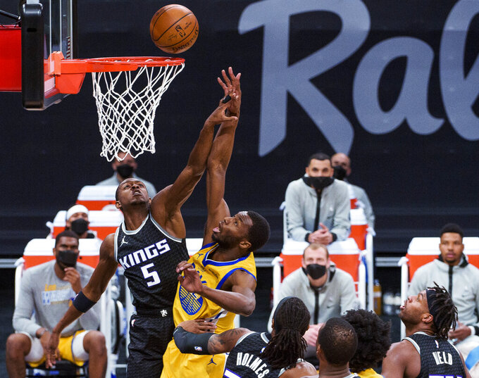 Golden State Warriors forward Andrew Wiggins lays the ball up as Sacramento Kings guard De'Aaron Fox (5) defends during the first quarter of an NBA basketball game in Sacramento, Calif., Thursday, March 25, 2021. (AP Photo/Randall Benton)