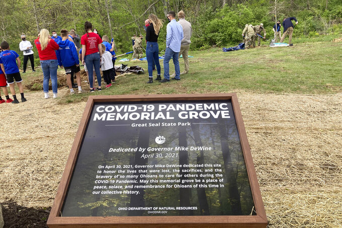 Various groups affected by the global coronavirus pandemic gather to plant trees on April 30, 2021, at Ohio's dedication of a new COVID-19 Pandemic Memorial Grove at Great Seal State Park near Chillicothe, Ohio. The country has begun finding ways to remember the more than 600,000 Americans who have died from the coronavirus, but the process is fraught compared to past memorial drives because of the politics. (AP Photo/Julie Carr Smyth)