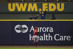 Members of the Milwaukee Brewers bullpen celebrate as Cincinnati Reds' Nicholas Castellanos (2) watches a two-run home run hit by Brewers' Justin Smoak during the third inning of a baseball game Monday, Aug. 24, 2020, in Milwaukee. (AP Photo/Aaron Gash)