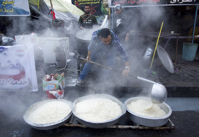 In this photo taken Sunday, Dec. 8, 2019, a volunteer chef prepares rice to be served to Iraqi protesters as part of a free meal, at the center of Baghdad, Iraq.  In Baghdad's Tahrir Square, there are the anti-government protesters demonstrating for a better future for Iraq, and there are the volunteers who feed them. From stuffed lamb and fish, to the giant pots of soups and rice to the plates of lentils and beans, there is no shortage of food to go around. Volunteers from the capital and southern provinces cook traditional dishes that reflect the country's rich cuisine and bring protesters together.  (AP Photo/Nasser Nasser)