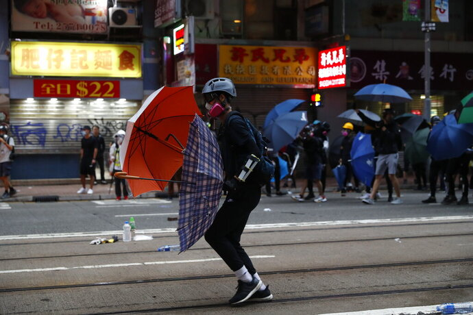 In this Oct. 6, 2019, photo, protestors clash with police in Hong Kong. Shouting