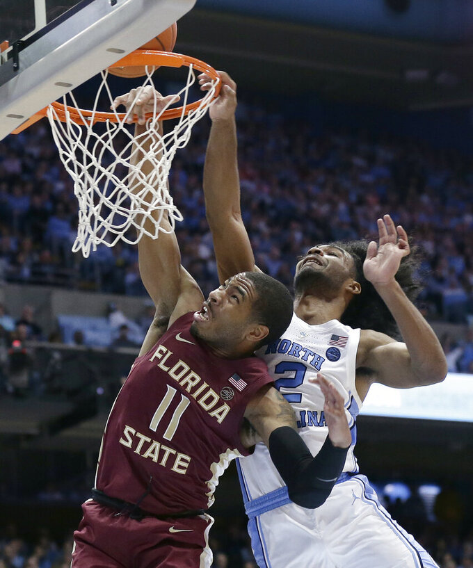 North Carolina's Coby White defends while Florida State's David Nichols (11) drives to the basket during the second half of an NCAA college basketball game in Chapel Hill, N.C., Saturday, Feb. 23, 2019. (AP Photo/Gerry Broome)