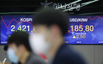 Currency traders watch computer monitors near the screens showing the Korea Composite Stock Price Index (KOSPI), left, and the foreign exchange rate between U.S. dollar and South Korean won at the foreign exchange dealing room in Seoul, South Korea, Friday, Aug. 14, 2020. Asian shares were mixed on Friday as investors studied fresh data out of China showing its recovery remains subdued. (AP Photo/Lee Jin-man)