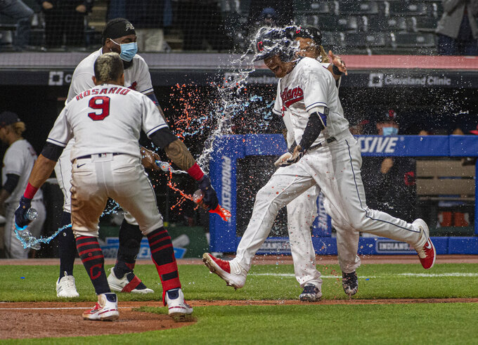 Cleveland Indians' Jordan Luplow gets drenched by Eddie Rosario and his teammates after hitting a two-run home run off Minnesota Twins relief pitcher Alex Colome during the tenth inning of a baseball game in Cleveland, Monday, April 26, 2021. (AP Photo/Phil Long)