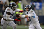 Tennessee Titans quarterback Ryan Tannehill, right, hands off to running back Derrick Henry during the second half of an NFL football game against the Seattle Seahawks, Sunday, Sept. 19, 2021, in Seattle. The Titans won 33-30 in overtime. (AP Photo/John Froschauer)