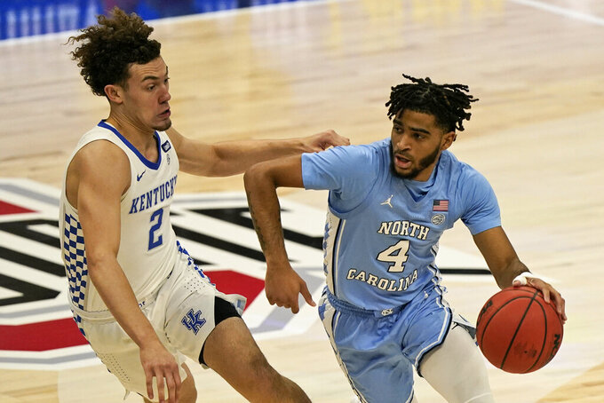 North Carolina's R.J. Davis (4) drives past Kentucky's Devin Askew (2) in the first half of an NCAA college basketball game, Saturday, Dec. 19, 2020, in Cleveland. (AP Photo/Tony Dejak)