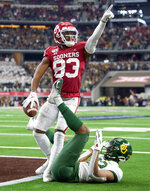 Oklahoma wide receiver Nick Basquine (83) celebrates a touchdown reception over Baylor safety JT Woods (22) during the second half of an NCAA college football game for the Big 12 Conference championship, Saturday, Dec. 7, 2019, in Arlington, Texas. Oklahoma won 30-23 in overtime. (AP Photo/Jeffrey McWhorter)