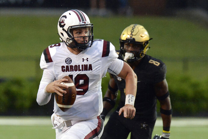 FILE - In this Sept. 22, 2018, file photo, South Carolina quarterback Jake Bentley (19) runs the ball ahead of Vanderbilt cornerback Joejuan Williams (8) during the second half of an NCAA college football game, in Nashville, Tenn. Back from a week off, South Carolina faces Tennessee on Saturday, Oct. 27. (AP Photo/Mark Zaleski, File)