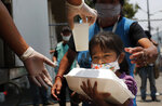 A child gets a meal from the mobile dining rooms program as people who have not been able to work because of the COVID-19 pandemic line up for a meal outside the Iztapalapa hospital in Mexico City, Wednesday, May 20, 2020. (AP Photo/Marco Ugarte)