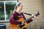 In this April 17, 2020, photo music therapist Kirsten Wells laughs while playing for a resident of Rising Mountains Assisted Living during her afternoon performance in Bigfork, Mont. She played songs like