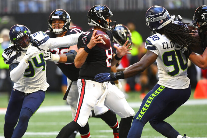 Atlanta Falcons quarterback Matt Schaub (8) works under pressure from the Seattle Seahawks in the pocket during the second half of an NFL football game, Sunday, Oct. 27, 2019, in Atlanta. The Seattle Seahawks won 27-20. (AP Photo/John Amis)