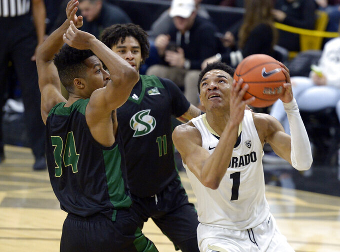 Colorado guard Tyler Bey, right, drives on Sacramento State forward Spencer Monteiro, left, and guard Brandon Davis in the second half of an NCAA college basketball game, Saturday, Nov. 30, 2019, in Boulder, Colo. (AP Photo/Cliff Grassmick)