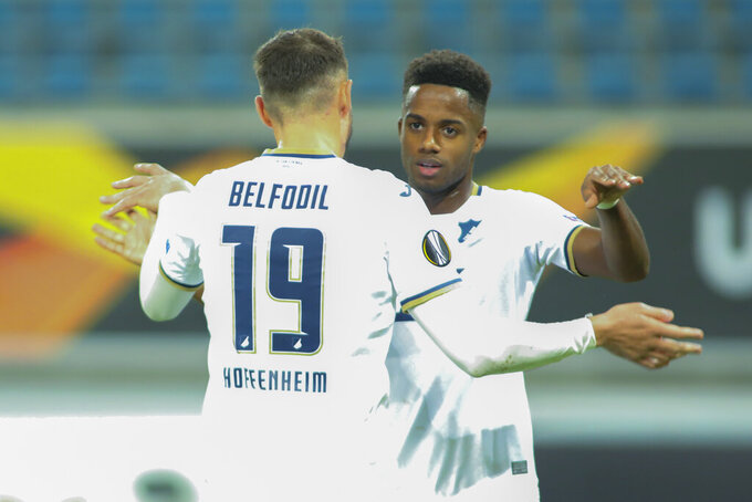 Hoffenheim's Ishak Belfodil, left, celebrates with teammate Ryan Sessegnon after scoring the opening goal during the Europa League Group L soccer match between Gent and Hoffenheim at the KAA Gent stadium in Gent, Belgium, Thursday, Oct. 29, 2020. (AP Photo/Olivier Matthys)