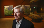 In this Wednesday, Oct. 23, 2019, photo, Richard Benefield, former executive director of the David Hockney Foundation, smiles as he looks inside the exhibit of Hockney's Yosemite artistic work, background, along with baskets from weavers from the Miwok and Mono Lake Paiute tribes on display at the Heard Museum in Phoenix.