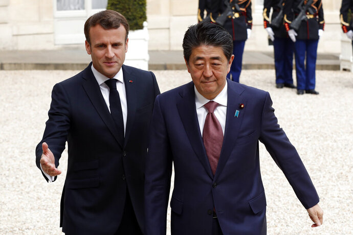 French President Emmanuel Macron, left welcomes Japan's Prime Minister Shinzo Abe wave before their talks at the Elysee Palace, Tuesday, April 23, 2019 in Paris. (AP Photo/Thibault Camus)