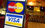 FILE - This April 22, 2005, file photo, shows logos for MasterCard and Visa credit cards at the entrance of a New York coffee shop. Visa and Mastercard are dropping out of Facebook's Libra project, a potentially fatal blow to the social network's plan for a worldwide digital currency, Friday, Oct. 11, 2019.  (AP Photo/Mark Lennihan, File)