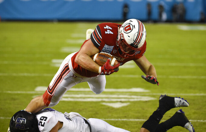 Utah tight end Jake Jackson (44) jumps over Northwestern defensive back Greg Newsome II (29) as he scores a touchdown during the first half of the Holiday Bowl NCAA college football game Monday, Dec. 31, 2018, in San Diego. (AP Photo/Denis Poroy)