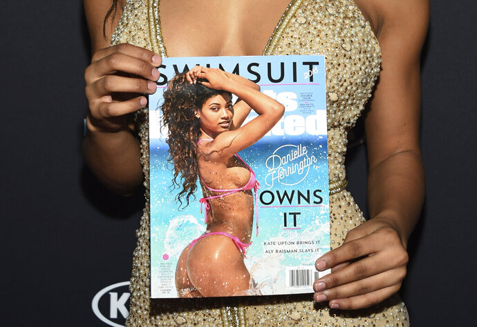 FILE - This Feb. 14, 2018, file photo shows a copy of Sports Illustrated held by Danielle Herrington attending its Swimsuit Issue launch party at Magic Hour at Moxy NYC Times Square in New York. The company that recently bought Sports Illustrated has found someone to run it: a small media company called Maven. Authentic Brands Group bought Sports Illustrated from publishing giant Meredith in May 2019. At the time, the companies said Meredith would run the magazine and the SI.com website for at least two years under a licensing deal. (Photo by Evan Agostini/Invision/AP, File)