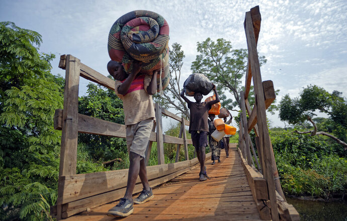 FILE - In this Thursday, June 8, 2017 file photo, from left, South Sudanese refugees Thomas Wani, 12, brother Peter Lemi, 14, mother Rose Sunday, and father Julius Lezu, cross a wooden bridge from South Sudan to Uganda at the Busia crossing, near Kuluba, in northern Uganda. The representative of the United Nations refugee agency in Uganda says
