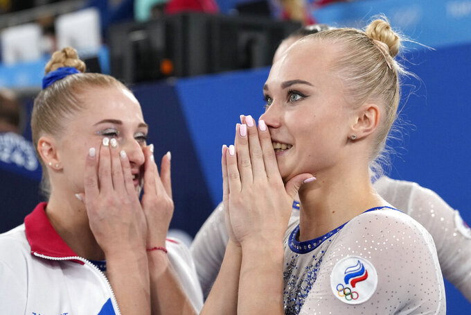 Russian Olympic Committee's artistic gymnastics women's team Liliia Akhaimova, left, and Angelina Melnikova celebrate after winning the gold medal for the artistic women's team at the 2020 Summer Olympics, Tuesday, July 27, 2021, in Tokyo. (AP Photo/Ashley Landis)