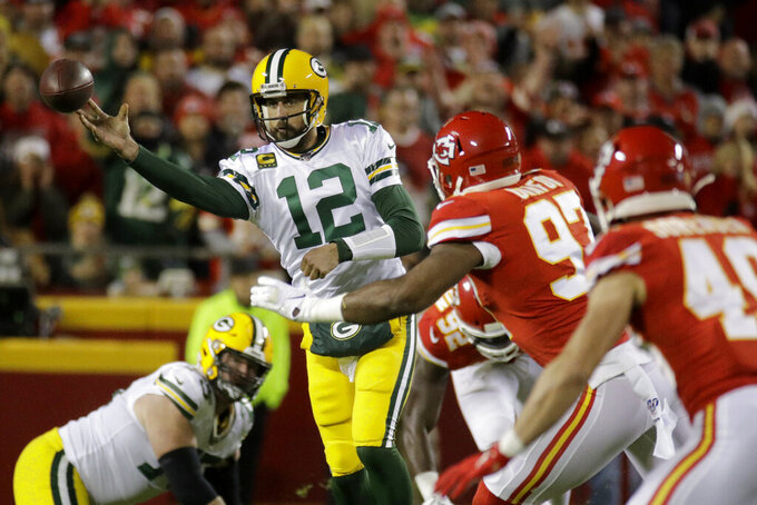 Green Bay Packers quarterback Aaron Rodgers (12) throws a pass against Kansas City Chiefs defensive end Alex Okafor (97) and safety Daniel Sorensen (49) during the first half of an NFL football game in Kansas City, Mo., Sunday, Oct. 27, 2019. (AP Photo/Charlie Riedel)
