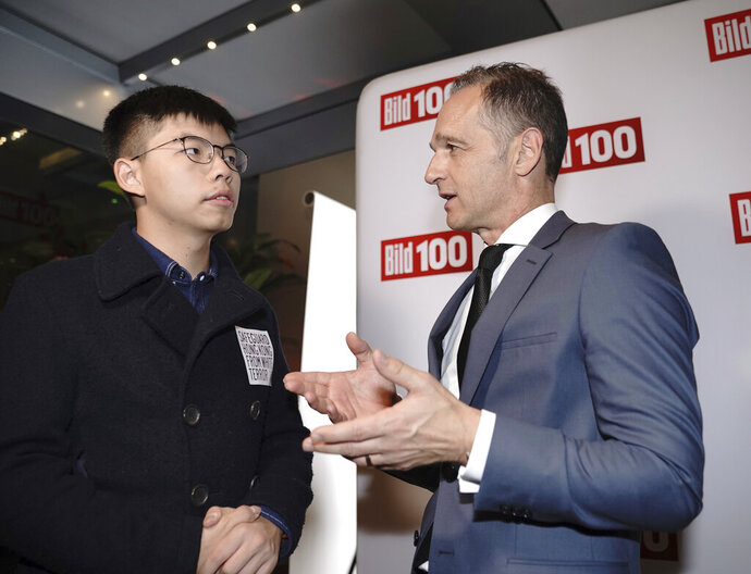 German Foreign Minister Heiko Maas, right, talks to Hong Kong activist Joshua Wong, left, during a reception of a German news paper in Berlin, Germany, Monday, Sept. 9, 2019. Wong will address the media during a press conference in Berlin on Wednesday, Sept. 11, 2019. (Michael Kappeler/dpa via AP)