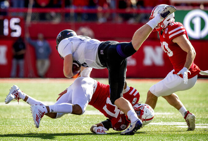 Northwestern quarterback Aidan Smith gets tackled by Nebraska's Braxton Clark (15), top, during the first half of an NCAA college football game, Saturday, Oct. 5, 2019 in Lincoln, Neb. (Francis Gardler/Lincoln Journal Star via AP)