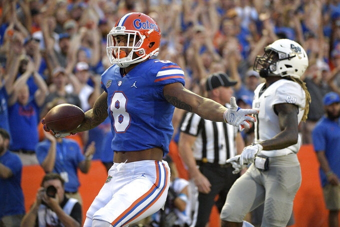 Florida wide receiver Trevon Grimes (8) celebrates after running into the end zone for a 34-yard receiving touchdown in front of Charleston Southern defensive back Brandon Rowland (7) during the first half of an NCAA college football game, Saturday, Sept. 1, 2018, in Gainesville, Fla. (AP Photo/Phelan M. Ebenhack)