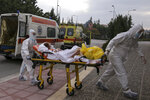 Medical personnel transfer a COVID-19 patient from a state to a private clinic which has been appropriated, in the northern city of Thessaloniki, Greece, Sunday, Nov. 29, 2020. Greece's Health ministry has forcibly appropriated two clinics and their staff in the country's second populated city, where the outbreak is the most severe. (AP Photo/Achilleas Chiras)