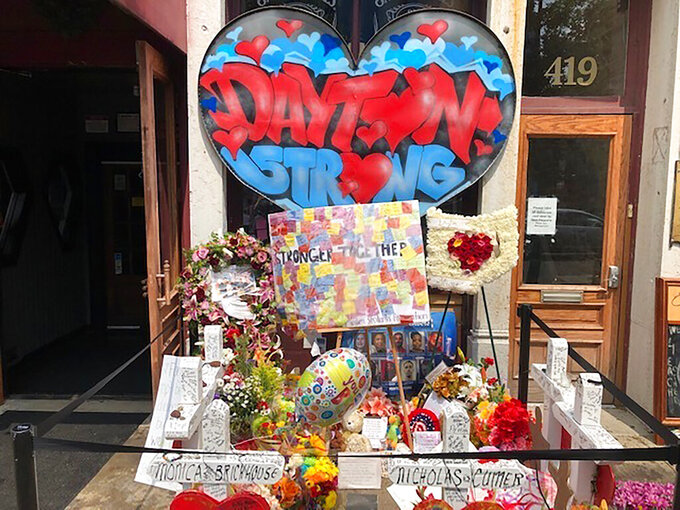 """FILE—In this file photo from Aug. 4, 2019, a makeshift memorial was placed outside Ned Peppers bar following a vigil at the scene of the mass shooting in Dayton, Ohio. Trey Landers, a Dayton native and senior guard on the University of Dayton basketball team was there when a masked gunman in body armor opened fire early that Sunday. He has now helped his basketball team to its best start ever at 26-2 and to No. 4 in the current Associated Press poll, its highest ranking in 64 years. People greet or email him to """"just thank me and my teammates for everything we're doing right now,"""" Landers said. """"Our team is helping pull the city together a little bit ... It's bigger than us.""""(AP Photo/Dan Sewell, File)"""