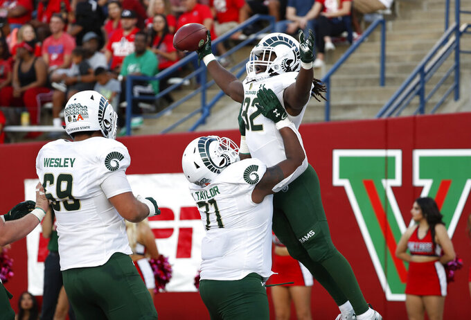 Colorado State running back Marcus McElroy (32) is hoisted in the air by Jeff Taylor (71) after a touchdown against Fresno State during the first half of an NCAA college football game in Fresno, Calif., Saturday, Oct. 26 2019. (AP Photo/Gary Kazanjian)