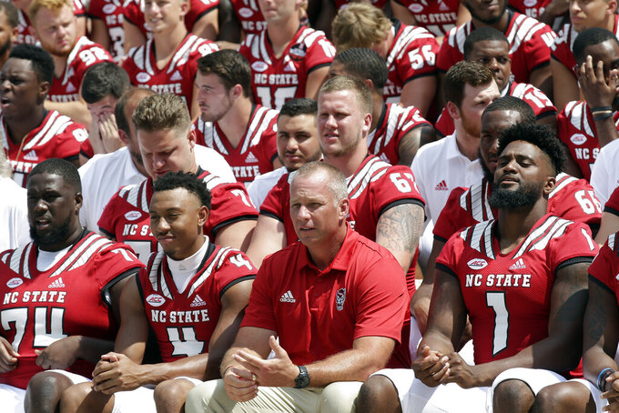 North Carolina State coach Dave Doeren, center, poses with players during a photo session at the team's NCAA college football media day in Raleigh, N.C., Sunday, Aug. 11, 2019. (AP Photo/Gerry Broome)