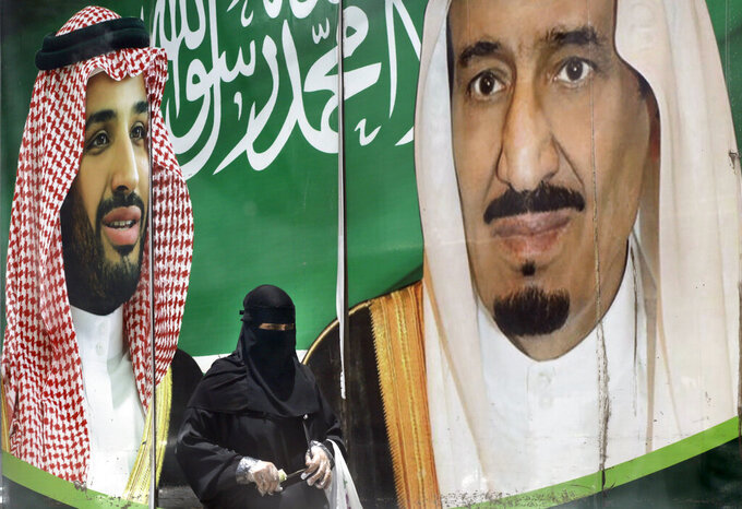 A woman walks past a banner showing Saudi King Salman, right, and his Crown Prince Mohammed bin Salman, outside a mall in Jiddah, Saudi Arabia, Monday, June 15, 2020. This was supposed to be Saudi Arabia's year to shine as host of the prestigious G20 gathering of world leaders. Instead, due to the coronavirus pandemic, the gathering this November will likely be a virtual meet-up, stripping its host of the pomp that would have accompanied televised arrivals on Riyadh's tarmac.  (AP Photo/Amr Nabil)