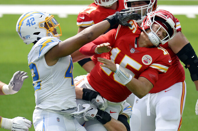 Kansas City Chiefs quarterback Patrick Mahomes, right, is pressured by Los Angeles Chargers linebacker Uchenna Nwosu (42) during the first half of an NFL football game Sunday, Sept. 20, 2020, in Inglewood, Calif. (AP Photo/Kyusung Gong)
