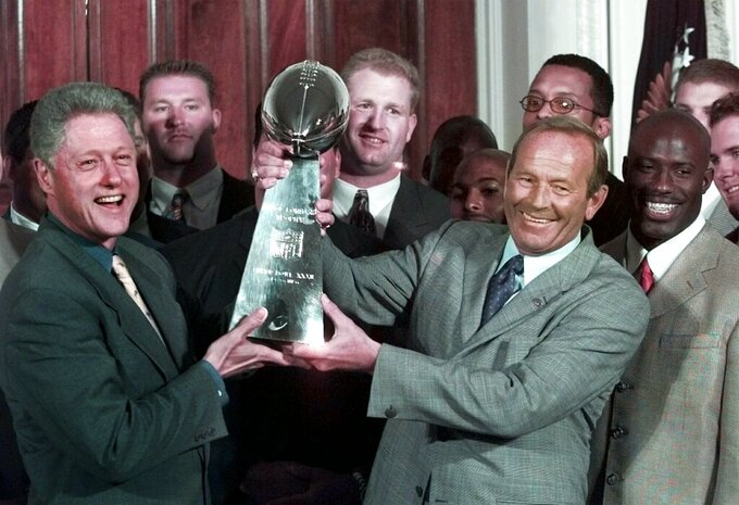 FILE - In this June 16, 1998, file photo, then-President Clinton, left, and Denver Broncos owner Pat Bowlen hold the Vince Lombardi Trophy during a ceremony at the White House where the president honored the Super Bowl XXXII champions. The late Pat Bowlen will be inducted into the Pro Football Hall of Fame in Canton, Ohio on Aug. 3, 2019.(AP Photo/Greg Gibson, File)