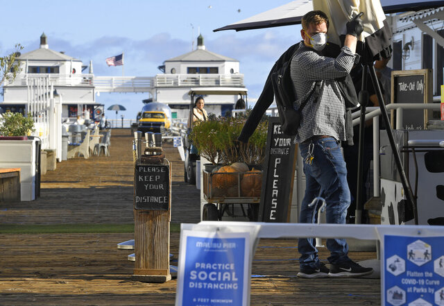 Signs are seen advising people to keep their distance from each other as a worker removes an umbrella in front of a restaurant on the Malibu Pier, Monday, March 23, 2020, in Malibu, Calif. Officials are trying to dissuade people from using the beaches after California Gov. Gavin Newsom ordered the state's 40 million residents to stay at home indefinitely. His order restricts non-essential movements to control the spread of the coronavirus that threatens to overwhelm the state's medical system. (AP Photo/Mark J. Terrill)