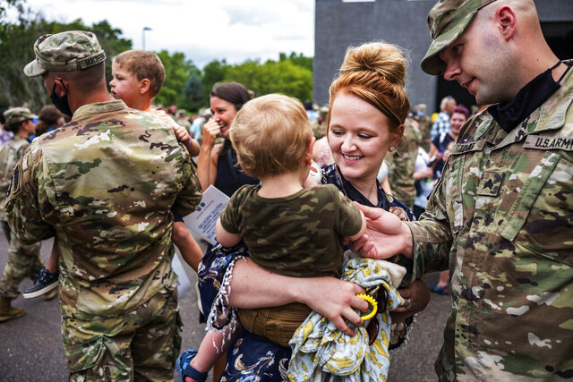 Sgt. Alex Tokar says goodbye to his wife Brittney and son Nolan, 2, Sunday, Aug. 9, 2020 before a year-long deployment to Naval Station Guantanamo Bay in support of Joint Task Force Guantanamo to provide base security. Colonel Brian Pfarr, far right addressed the approximately 150 soldiers from the Stillwater-based 34th Military Police Company who will deploy (Richard Tsong-Taatarii/Star Tribune via AP)