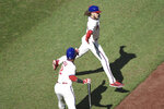 Philadelphia Phillies' Alec Bohm, right, who scored on an RBI double, is greeted by teammate Jean Segura, left, during the first inning of a baseball game against the Toronto Blue Jays, Sunday, Sept. 20, 2020, in Philadelphia. (AP Photo/Michael Perez)