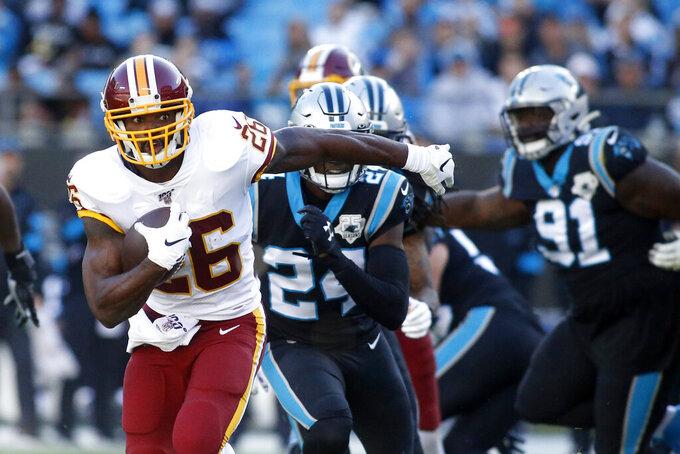 El corredor de los Redskins de Washington Adrian Peterson se escapa de la defensiva de los Panthers de Carolina en el triunfo de su equipo el primero de diciembre del 2019. (AP Photo/Brian Blanco)