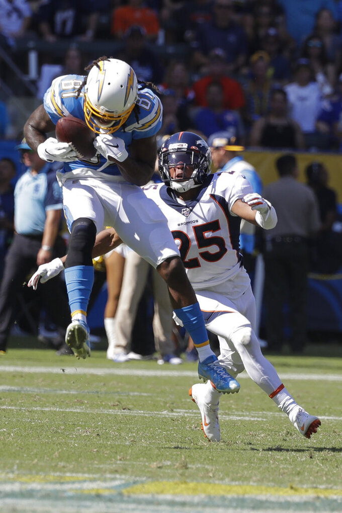 Los Angeles Chargers wide receiver Mike Williams catches a pass as Denver Broncos cornerback Chris Harris looks on during the first half of an NFL football game Sunday, Oct. 6, 2019, in Carson, Calif. (AP Photo/Alex Gallardo)