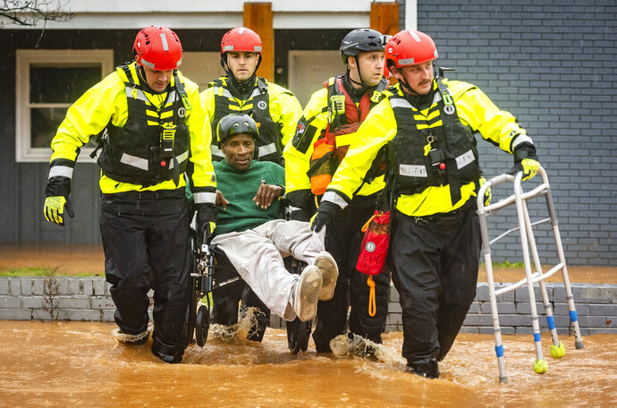 Winston-Salem Fire Department firefighters with the Rescue Task Force rescue James Benjamin from his home at Liberty Landing Apartments as flood waters rise around the building on Thursday, Feb. 6, 2020, in Winston-Salem, N.C. (Andrew Dye/The Winston-Salem Journal via AP)