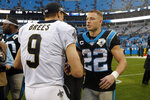 New Orleans Saints quarterback Drew Brees (9) and Carolina Panthers running back Christian McCaffrey (22) speak following an NFL football game in Charlotte, N.C., Sunday, Dec. 29, 2019. (AP Photo/Brian Blanco)