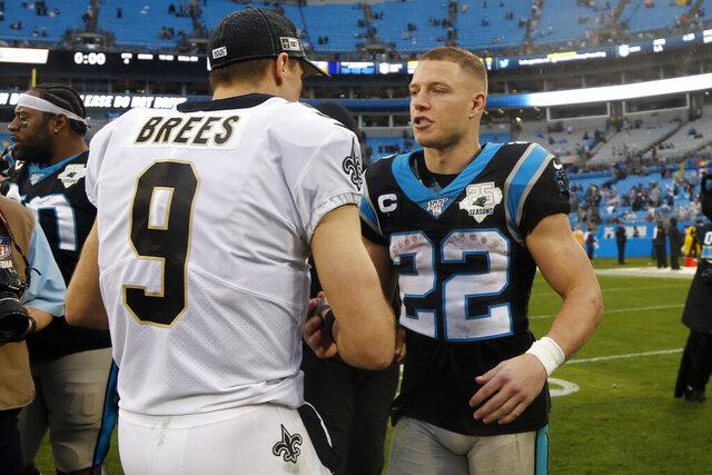 New Orleans Saints quarterback Drew Brees (9) and Carolina Panthers running back Christian McCaffrey (22) speak following an NFL football game in Charlotte, N.C., Sunday, Dec. 29, 2019. (AP Photo/Brian Blanco)
